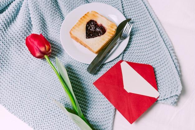 Toast mit marmelade in herzform mit tulpe auf schal