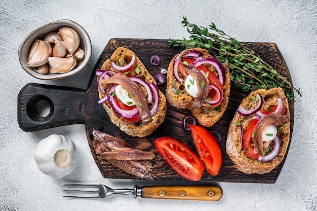 Toast mit olivenöl, kräutern, tomaten und würzigen sardellenfilets