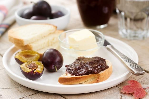 Toast mit pflaumenschokoladenmarmelade. frühstück im garten. rustikaler stil