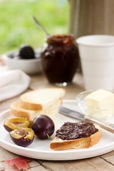 Toast mit pflaumenschokoladenmarmelade und kakao. frühstück im garten. rustikaler stil