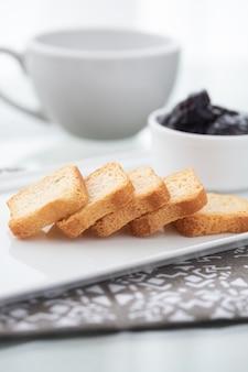 Toast mit preiselbeermarmelade und einer tasse kaffee auf weiß
