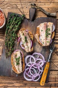 Toast mit sardine, frischkäse und zwiebeln. hölzerner hintergrund. ansicht von oben.