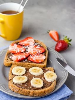 Toast mit schokolade und früchten auf einem grauen teller. erdbeeren und bananen auf steinküchentisch