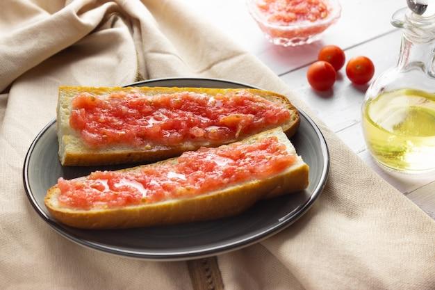 Toast mit tomaten, traditionelles spanisches frühstück. olivenöl, heller hintergrund.