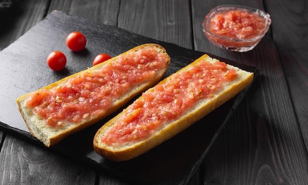 Toast mit tomaten, traditionelles spanisches frühstück. olivenöl, schwarzer hintergrund. pan tumaka