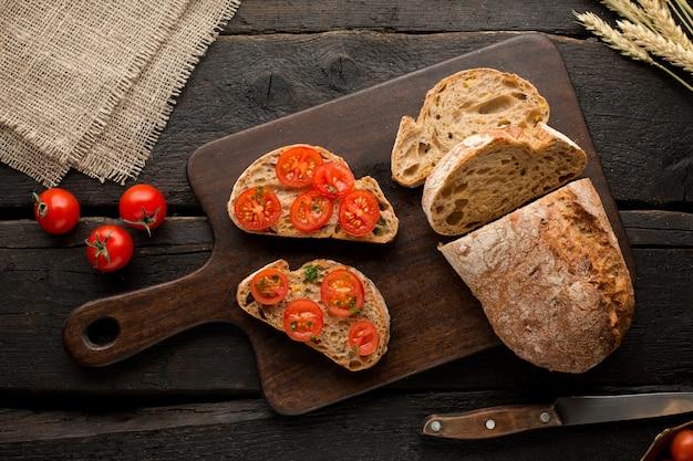 Toast mit tomaten und brot auf einem brett