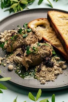 Toast und hühnerleberpastete mit halva und pflaumen