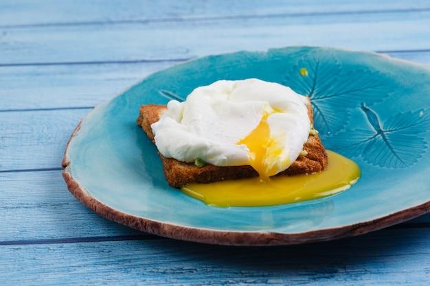 Toast und poschiertes ei mit avocado auf einer platte auf holztisch