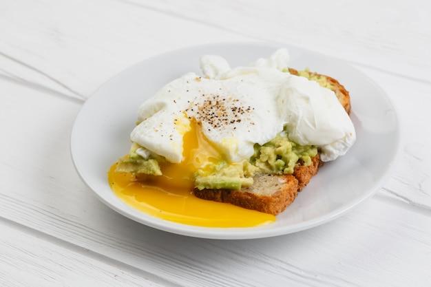 Toast und poschiertes ei mit avocado auf einer platte auf weißem holztisch