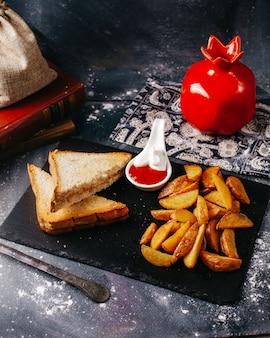 Toast von vorne mit bratkartoffeln und ketchup mit mayonaonaise auf der grauen oberfläche