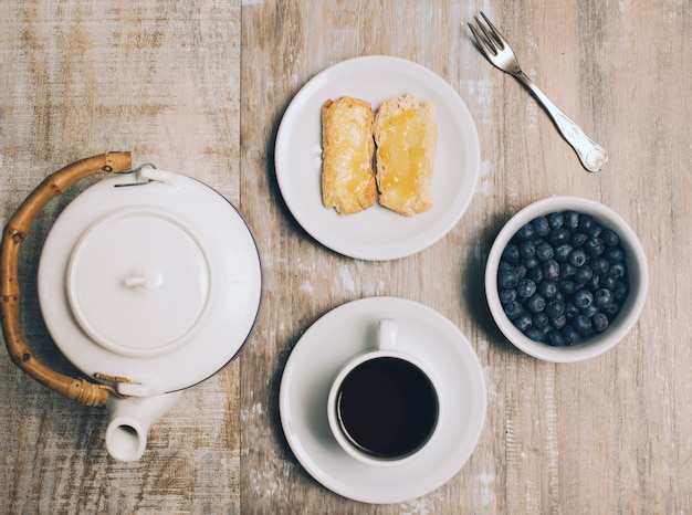 Toastbrot; kaffeetasse; blaubeeren und teekanne auf hölzernen hintergrund