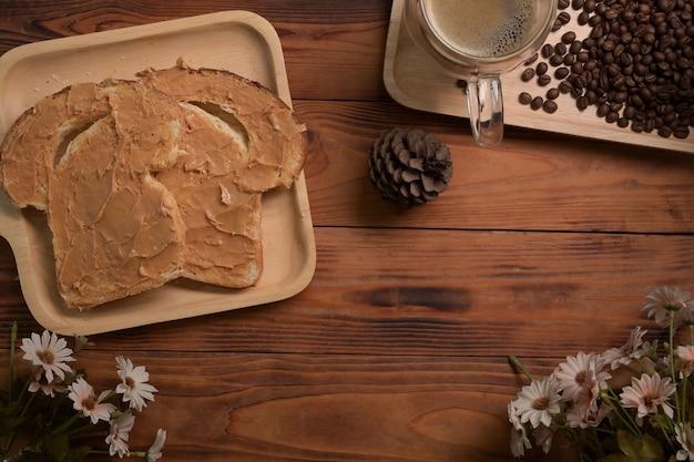 Toastbrot mit erdnussbutter und kaffeetasse auf holztisch.