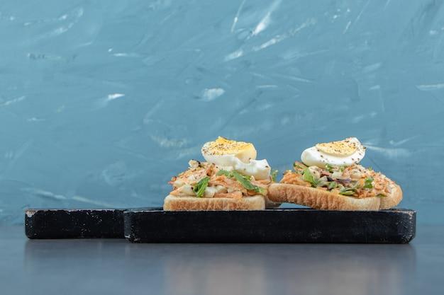 Toastbrot mit gekochten eiern auf schwarzem brett