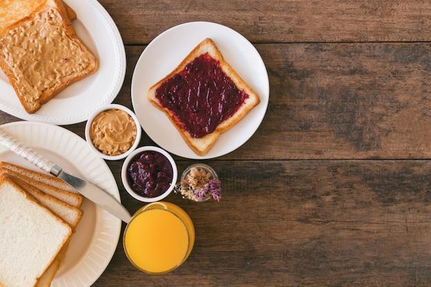 Toastbrot mit hausgemachter erdbeermarmelade und erdnussbutter, serviert mit orangensaft