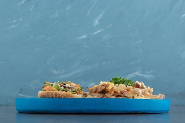 Toastbrot mit salat und ei auf blauem teller.