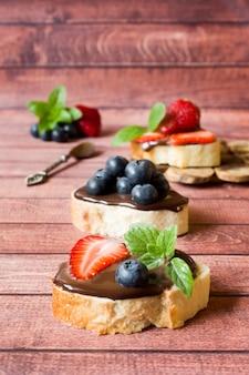 Toastbrot mit schokoladenpaste und erdbeerblaubeerminze auf dem tisch