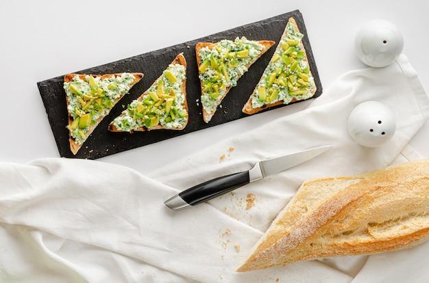 Toastbrot mit spinat, ricotta und avocado auf schwarzem brett