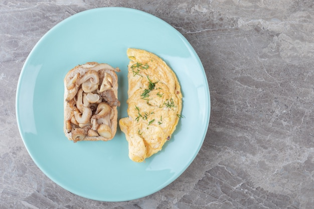 Toastbrot und omelett auf blauem teller.