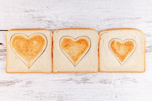 Toastbrotherzen auf holztisch, konzept des frühstücks in der glücklichen familie
