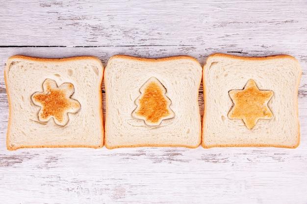 Toastbrotscheiben mit geröstetem ausschnitt in form einer tanne und einer schneeflocke