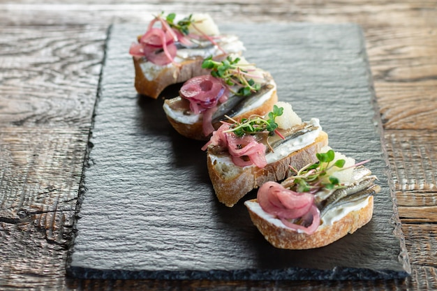 Toasten oder offene sandwiches mit fisch, käse, zwiebeln, microgreens und kaviar