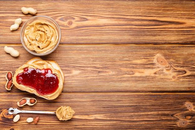 Toastsandwich mit erdnussbutter. löffel und glas erdnussbutter, marmelade und erdnüsse zum kochen des frühstücks auf braunem holz