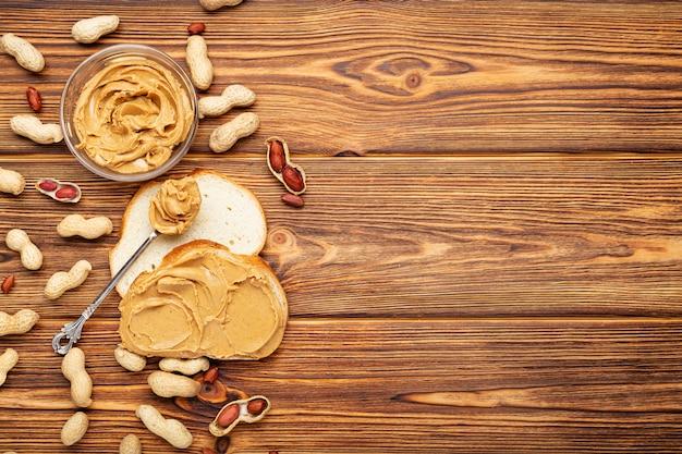 Toastsandwich mit erdnussbutter. löffel und glas erdnussbutter und erdnüsse zum kochen des frühstücks auf einem braunen hölzernen hintergrund. cremige erdnusspaste flach lag mit platz für text.
