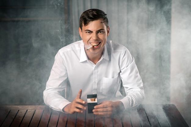 Tobacco evil: ein porträt eines jungen mannes, der mit einem bösen blick auf einem rauchigen hintergrund posiert und eine packung zigaretten in den händen und eine brennende zigarre im mund hält. schlechte gewohnheiten werden getötet.