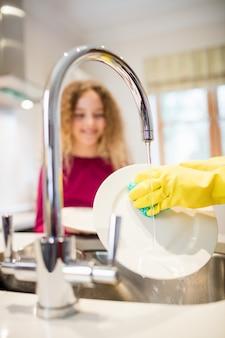 Tochter auf mutter schaut, während teller in der küche waschen