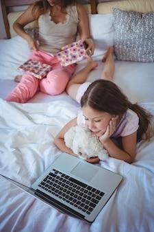 Tochter benutzt laptop auf bett und mutter öffnet ihr geschenk
