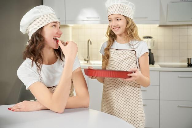 Tochter, die backform hält, mutter, der keks schmeckt.