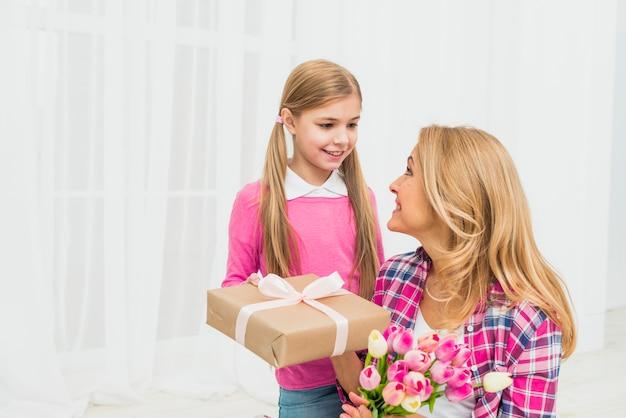 Tochter, die der mutter mit blumen geschenk gibt