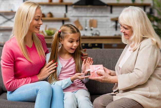 Tochter, die ein geschenk von ihrer großmutter empfängt