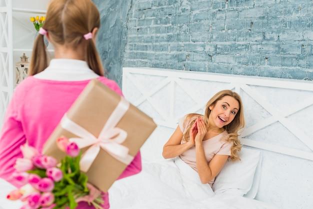 Tochter, die geschenk und tulpen für glückliche mutter im bett hält