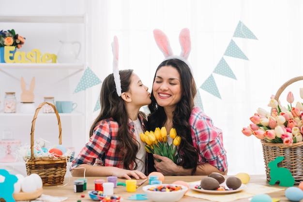 Tochter, die ihre mutter auf ostern-tagesfeier küsst
