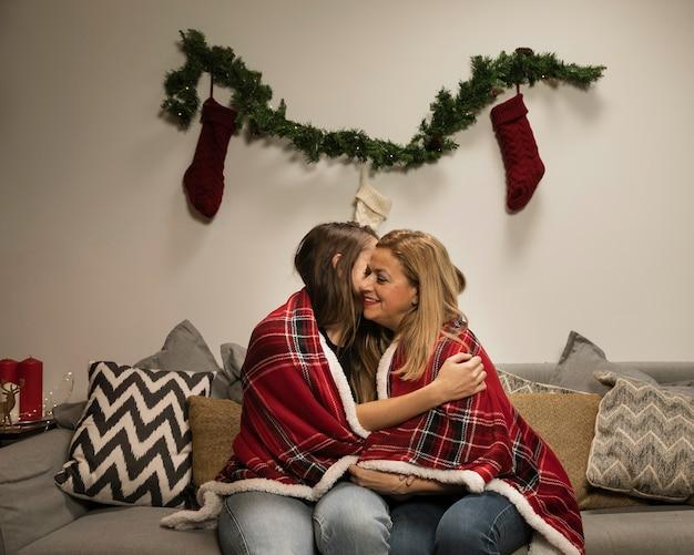 Tochter, die ihre mutter für weihnachten umarmt