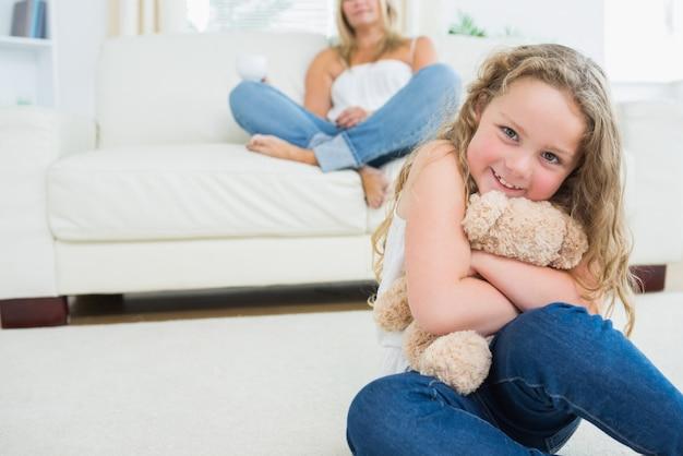 Tochter, die ihren teddybären umarmt