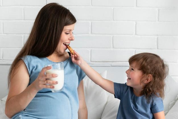 Tochter, die ihrer mutter ein plätzchen gibt, um zu essen