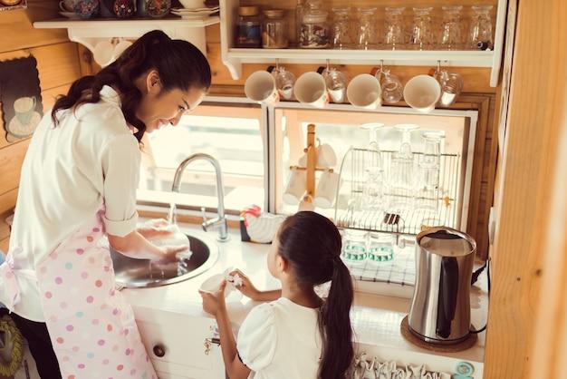 Tochter, die ihrer mutter in der küche hilft, teller zu waschen, das glas waschend