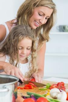 Tochter, die lernt, wie man gemüse schneidet