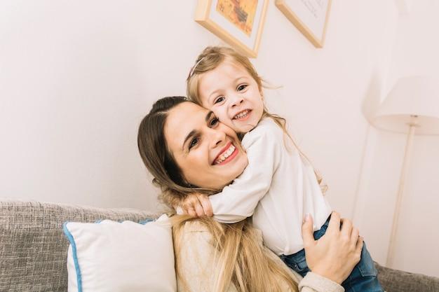 Tochter, die mutter auf sofa umarmt