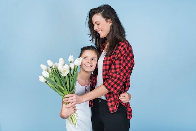 Tochter, die mutter umarmt und ihren tulpen gibt