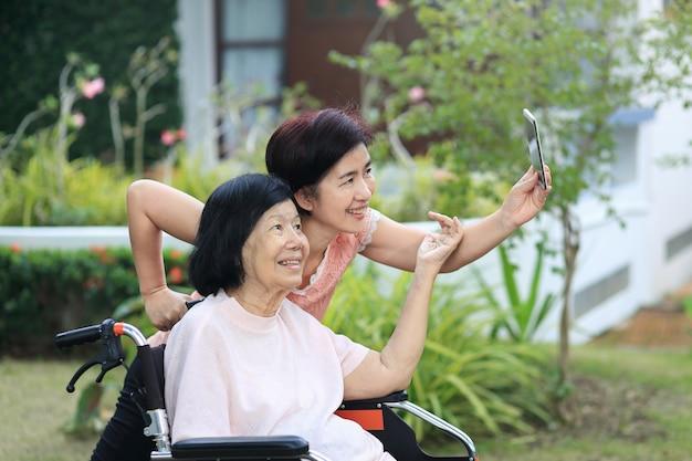 Tochter, die sich um die ältere asiatische frau kümmert, macht selfie, glücklich, lächelt im hinterhof.
