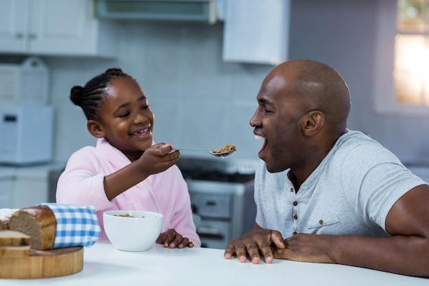 Tochter füttert vater mit frühstück