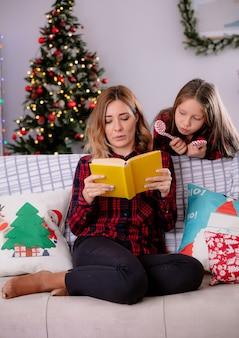 Tochter hält zuckerstange und schaut auf das lesebuch ihrer mutter, das auf der couch sitzt und die weihnachtszeit zu hause genießt