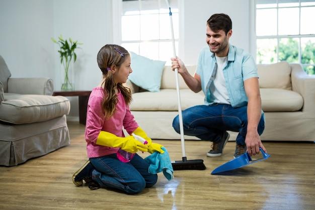 Tochter hilft vater, den boden zu reinigen