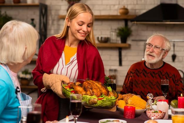 Tochter holt den köstlichen truthahn am tisch