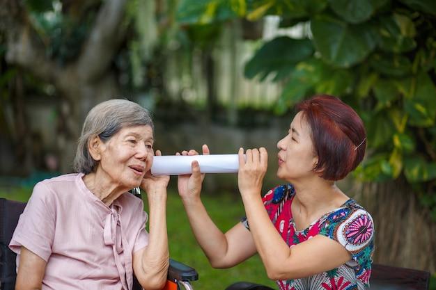 Tochter im gespräch mit hörgeschädigter älterer frau, mit papierrohr