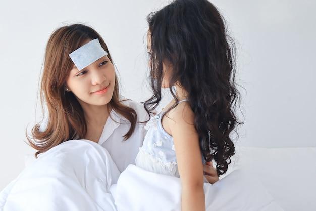 Tochter im kindesalter, die sich um eine mutter kümmert, die zu hause krank ist liebe zwischen mutter und kind