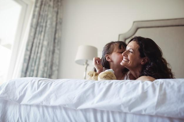 Tochter küsst ihre mutter auf die wange im schlafzimmer